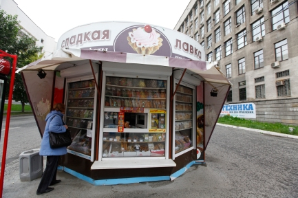 Ekaterinbourg, Russie, Septembre 2013. Dans les villes moyennes, ces kiosques sont le seul rappel évident que la société de consommation se développe en Russie, où les supermarchés restent peu visibles. En fait, il nous faudra une semaine pour comprendre que, souvent, les boutiques n'ont pas pignon sur rue. On les trouve dans les cours des maisons, dans les étages des immeubles, en entresol… Combien de fois nous tournerons en rond, cherchant une adresse indiquée par le Lonely Planet, sans jamais trouver la porte du restaurant ou de la boulangerie tant convoitée !