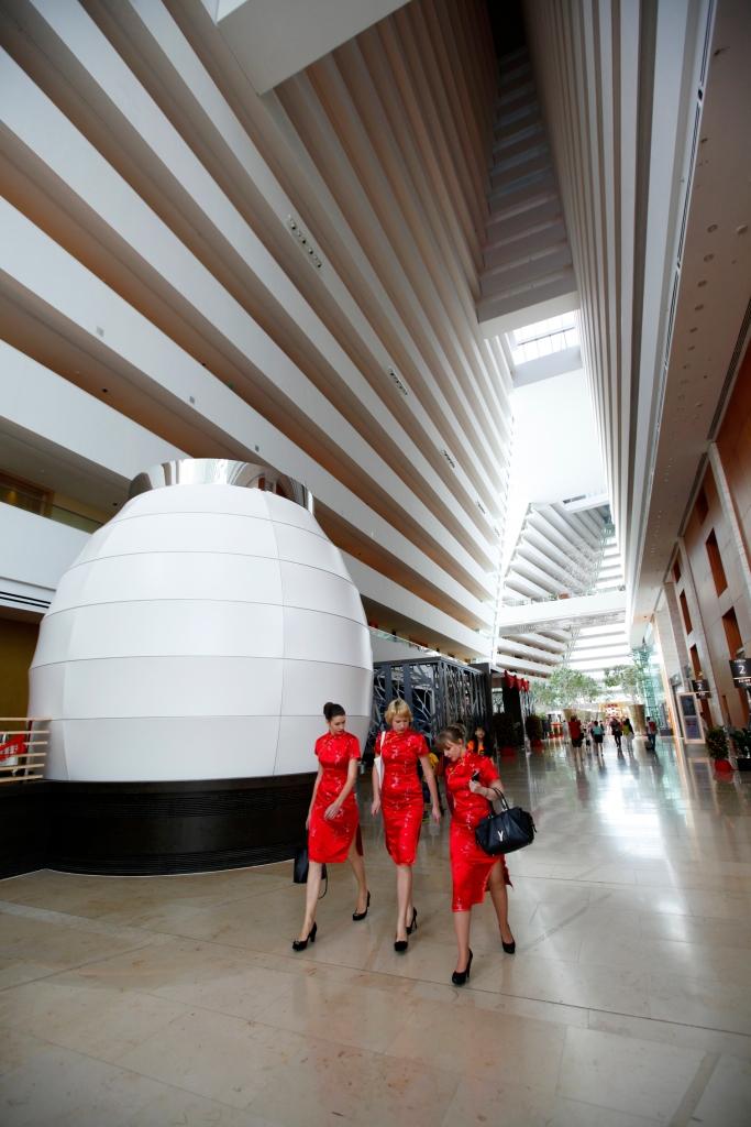Singapore - Orange stewardesses walking down Marina bay Sands